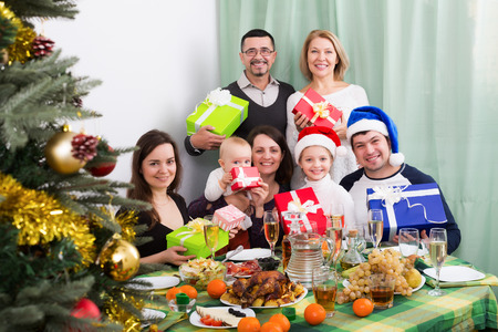granny and grandad: Happy mature parents with adult kids and grandchildren celebrating Merry Christmas