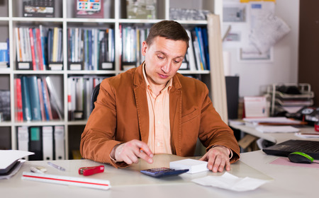 Attentive clerk calculates the cost estimate in the office Stock Photo