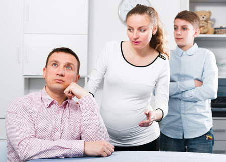 Middle-aged woman and her son arguing with husband at home