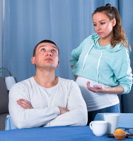 Middle-aged husband and pregnant wife quarrelling with each other at home Stock Photo