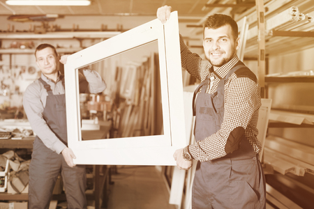 calm male professional labours with finished PVC profiles and windows at factory Stock Photo