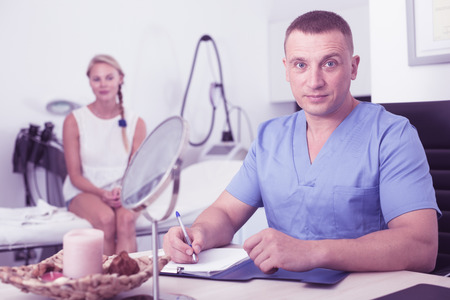 Doctor is writing the conclusion about result of examination of female client in estetic clinic. Reklamní fotografie