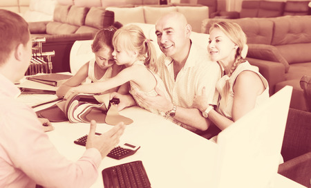 Positive family with kids are consulting with assistant about the color of furniture Stock Photo