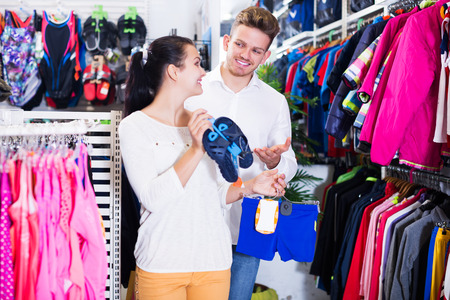 Positive young family choosing children's swimwear in sports store Stock Photo