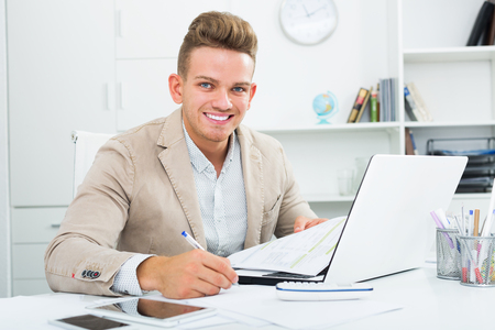 Successful man working with documents and laptop in office Stock Photo