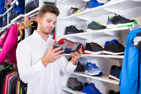 Young man choosing new sneakers in sports store