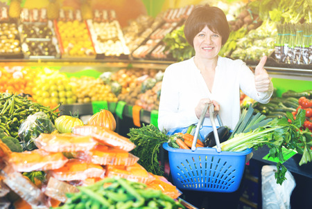 ensaladilla rusa: Adult cheerful female taking vegetables with basket on the store