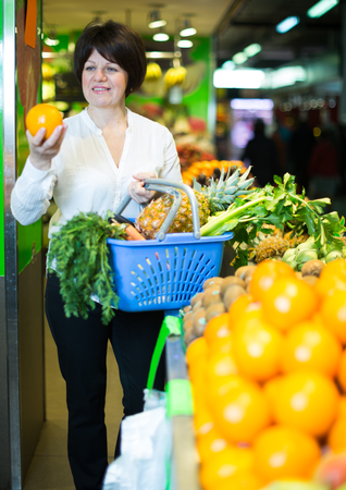 Adult cheerful female taking fruits with basket on the store
