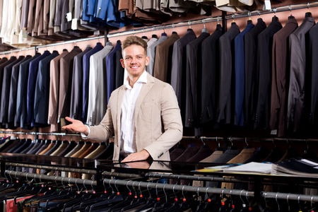 Happy male seller demonstrating numerous suits in men's cloths store