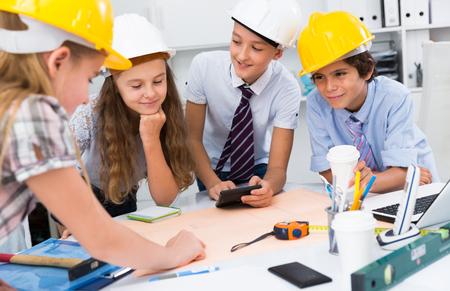 Adolescentes en color casco ingenieros discutiendo borrador en la mesa