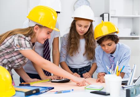 Group of children in helmet talking about building near laptop  Stockfoto
