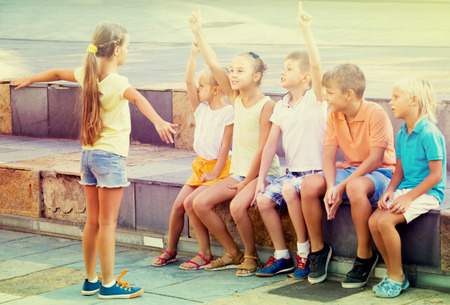 Cheerful boys and girls in school age having fun playing charades Imagens
