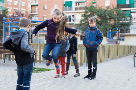 アメリカの子供たちがゲームをジャンプと屋外笑ってゴム バンドの演奏