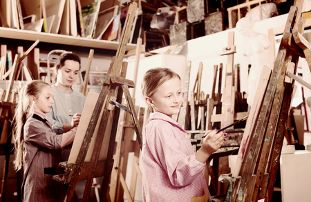 diligent: Children diligently draw the lesson of drawing in the  art workshop