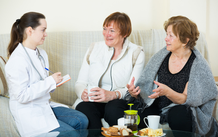 Two senior women discussing health problems with female therapeutist