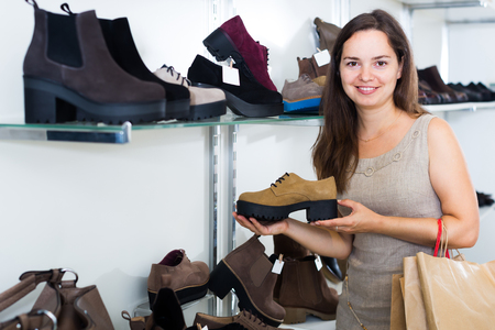 brogues: Portrait of smiling woman selecting loafers in footgear center