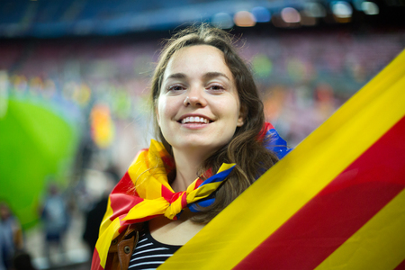 smiling female football fan with flag of Catalonia at stadium