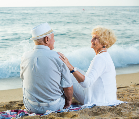 Portrait of mature female and male in hat sitting on the beach Imagens