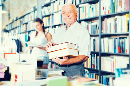 Mature man is showing book that he bought in bookstore. Stock Photo