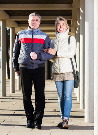 Happy senior couple walking along corridor fenced with columns Stock Photo