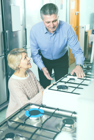 happy mature couple chooses in shop of household appliances gas stove with oven to itself home Stock Photo