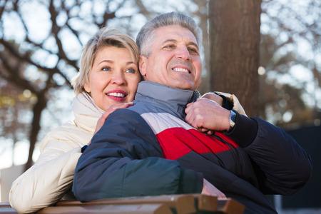 Mari senior positif et femme étreignant les uns les autres, assis sur un banc de parc Banque d'images - 88879484