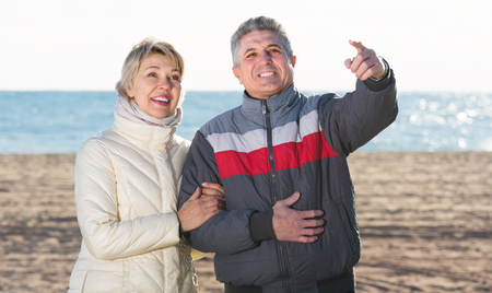 attract attention: happy husband and wife have together rest and show each other hands interesting things outdoors Stock Photo