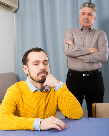 Mature father teaches and instructs his young son at table at home Stock Photo