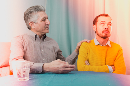 Mature father and his son are serious conversation at home and solve problems Stock Photo
