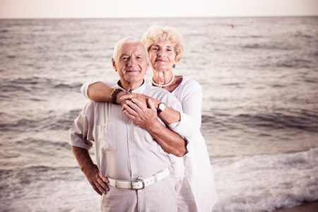 Portrait of mature female and male standing on the sea coast Stock Photo