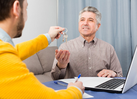 Mature man and young man signed contract of rent apartments and hand over keys
