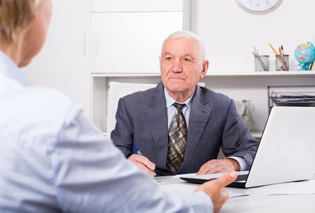 Smiling man manager talking with important client in his office