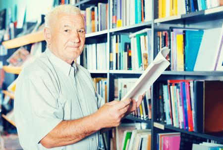 Het oude positieve Italiaanse mannetje kiest boek voor het lezen in vrije tijd in boekhandel.
