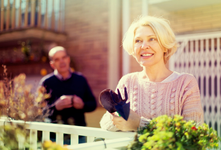 Mature woman in patio with gardening accessories with her husband in the background Stock Photo