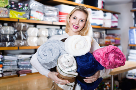 Young happy  female customer boasting purchased home textiles in textile shop