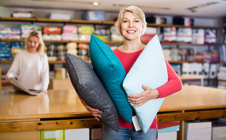 boasting: positive aged woman enjoying purchased home textiles in textile shop