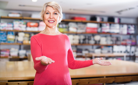 Cheerful  mature woman seller displaying various home textiles in shop Stock Photo