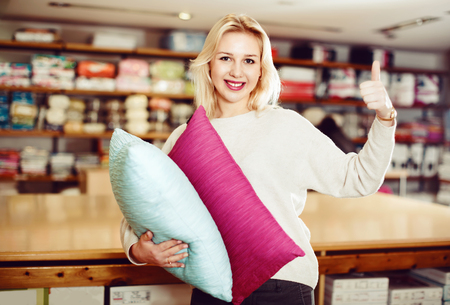 boasting: Cheerful  female customer boasting purchased home textiles in textile shop
