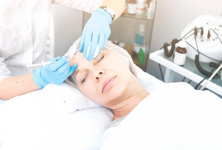 Joven médico femenina usando la inyección en los procedimientos de belleza para la mujer cliente
