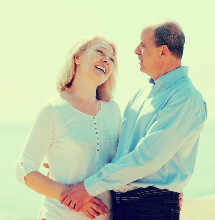 Portrait of happy  mature couple against sea in background