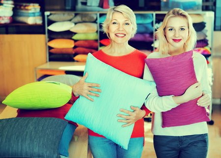 boasting: Happy cheerful positive girl and mature woman customers showing bought pillows in home textile shop