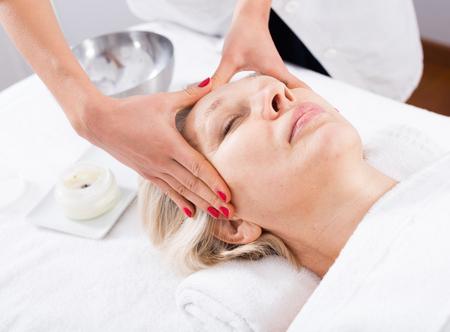 Madura cliente de la mujer que tiene procedimiento de masaje de cara en salón de belleza