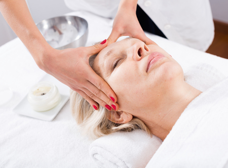 Mature woman client having face massage procedure in beauty salon Stock Photo