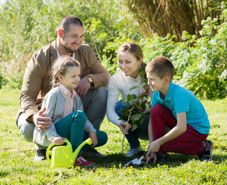 Smiling family with two teenagers placing a new tree in the soil Stock Photo