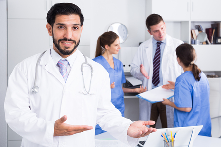 Bearded doctor making welcome gesture, politely inviting patient in medical office
