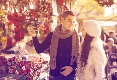 Happy  girl with boyfriend choosing Christmas decoration at Barcelona. Selective focus Banco de Imagens