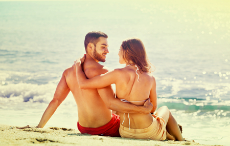 Young couple laying on sandy beach at sea shore in a sunny day