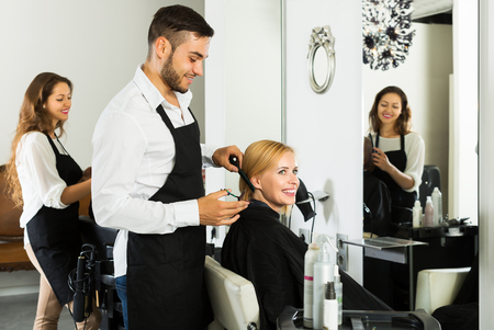 Happy man hairdresser doing hairstyle for young men