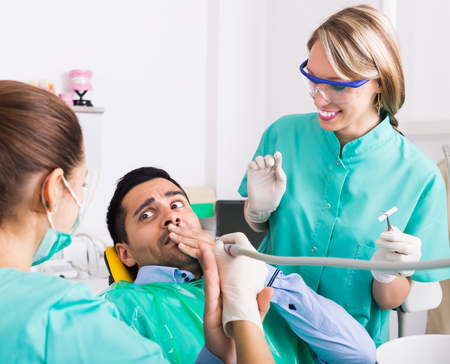 Terrified and dispair client and dental clinic crew during check up