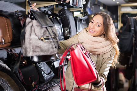 Ordinary girl choosing bag among assortment in store  Stock Photo